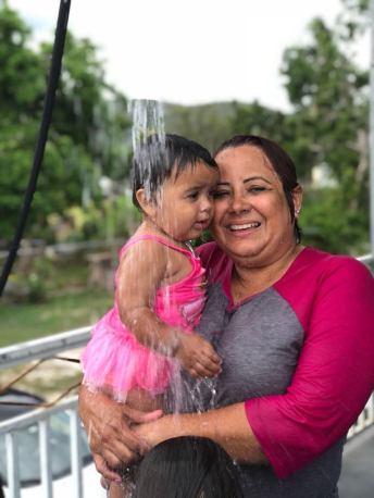 bebe y abuela jugando con agua en la manguera