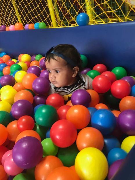 pequena bebe jugando en area de juegos y piscina de bolas